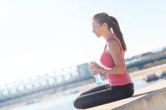 Молодая женщина сидя на речном береге Стоковое Изображение