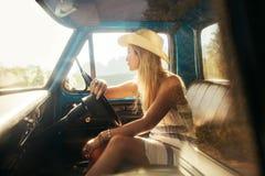 Молодая женщина сидя на сиденье водителя автомобиля Стоковая Фотография