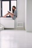 Молодая женщина сидя на силле окна читая книгу стоковое фото