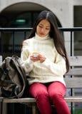 Молодая женщина сидя на скамейке в парке с сотовым телефоном и наушниками Стоковое Фото