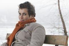 Молодая женщина сидя на скамейке в парке Стоковые Изображения RF