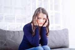 Молодая женщина сидя на софе имея мигрень головной боли Стоковая Фотография