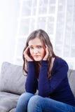 Молодая женщина сидя на софе имея мигрень головной боли Стоковые Фотографии RF