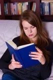 Молодая женщина сидя на софе дома, читающ книгу Стоковые Фотографии RF