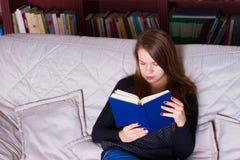 Молодая женщина сидя на софе дома, читающ книгу Стоковые Изображения RF