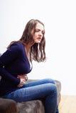 Молодая женщина сидя на софе страдая от боли в животе Стоковые Фотографии RF