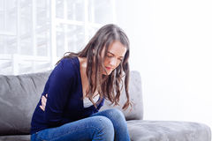 Молодая женщина сидя на софе страдая от боли в животе Стоковые Изображения