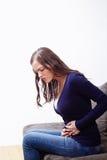 Молодая женщина сидя на софе страдая от боли в животе Стоковое Фото
