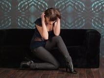 Молодая женщина сидя на софе Стоковое фото RF