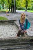 Молодая женщина сидя на спортивной площадке в парке города стоковые фотографии rf