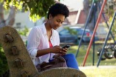 Молодая женщина сидя на стенде посылая текстовое сообщение Стоковые Фото