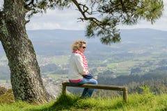 Молодая женщина сидя на стенде смотря природу Стоковая Фотография