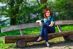 Молодая женщина сидя на стенде Стоковая Фотография RF