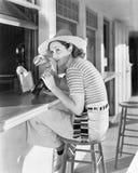 Молодая женщина сидя на счетчике выпивая кока-колу (все показанные люди более длинные живущие и никакое имущество не существует п стоковые фото