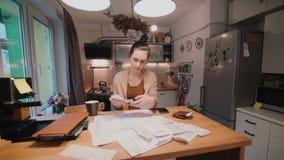 Молодая женщина сидя на таблице в кухне и расчетливые счеты после ходить по магазинам Домашний отдел учета видеоматериал