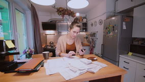 Молодая женщина сидя на таблице в кухне и расчетливых счетах Домашний отдел учета Проверять счеты видеоматериал
