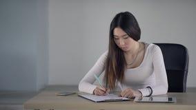 Молодая женщина сидя на таблице и писать с ручкой на бумаге внутри помещения сток-видео