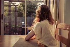 Молодая женщина сидя на таблице и смотря вне окно стоковая фотография rf