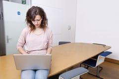 Молодая женщина сидя на таблице работая на компьтер-книжке Стоковые Изображения