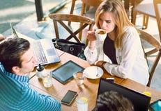Молодая женщина сидя на таблице с ее друзьями в кафе Стоковые Фотографии RF