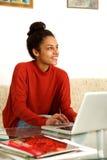 Молодая женщина сидя на таблице с компьтер-книжкой Стоковые Фотографии RF