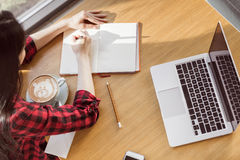 Молодая женщина сидя на таблице с кофе и компьтер-книжкой и писать в тетради Стоковое Изображение