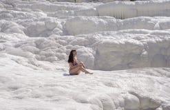 Молодая женщина сидя на травертинах в Pamukkale Стоковое Фото