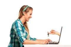 Молодая женщина сидя на ходить по магазинам стола онлайн Стоковое Изображение