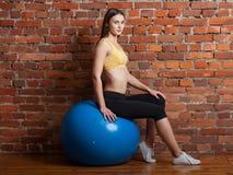 Молодая женщина сидя на шарике, на предпосылке кирпичной стены стоковые фотографии rf