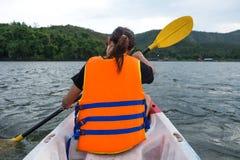 Молодая женщина сидя на шлюпке каное и гребя в озере Стоковая Фотография