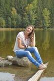 Молодая женщина сидя около озера Стоковое фото RF