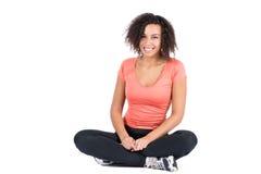 Молодая женщина сидя положив ногу на ногу стоковые изображения rf