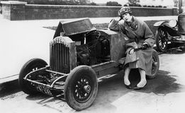Молодая женщина сидя рядом с малым автомобилем смотря двигатель внутри не верить (все показанные люди нет более длинные живущих и Стоковое Фото