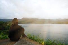 Молодая женщина сидя самостоятельно на скале фронт ее имеет море и su Стоковые Фото