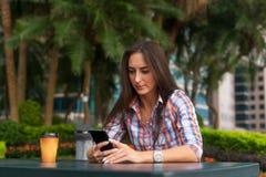 Молодая женщина сидя outdoors читая и печатая сообщения на ее smartphone Стоковые Изображения