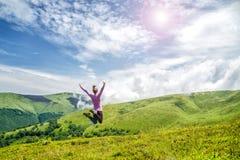 Молодая женщина скача в горы стоковая фотография rf