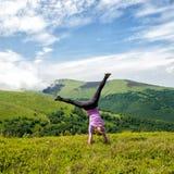 Молодая женщина скача в горы стоковое фото