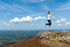 Молодая женщина скача на предпосылку гор Стоковое Фото