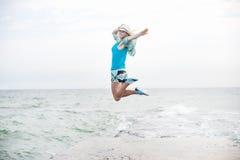 Молодая женщина скача на пляж Стоковые Фотографии RF