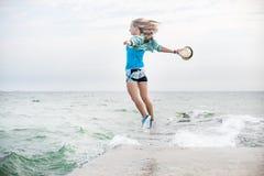 Молодая женщина скача на пляж Стоковое Фото