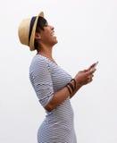 Молодая женщина смеясь над и держа мобильным телефоном Стоковое Изображение