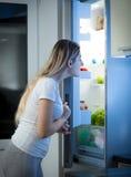 Молодая женщина смотря внутри холодильника для что-то съесть Стоковое Изображение RF
