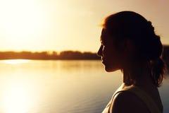 Молодая женщина смотря в расстояние на заходе солнца Стоковое фото RF