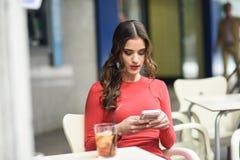 Молодая женщина смотря ее smartphone сидя в кафе Стоковое Изображение
