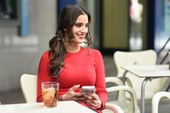 Молодая женщина смотря ее smartphone сидя в кафе Стоковые Фото