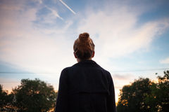 Молодая женщина смотря заход солнца в расстоянии Стоковое фото RF