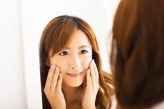 молодая женщина смотря зеркало в спальне Стоковое Фото