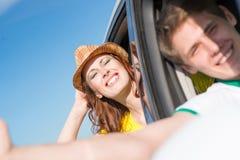 Молодая женщина смотря из окна автомобиля Стоковая Фотография