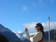 Молодая женщина смотря мобильный телефон, в установке внешних/природы Стоковое Фото