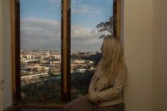 Молодая женщина смотря на городе от окна стоковое фото rf